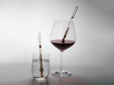 Edelsteinstab in gefülltem Wasser- und Weinglas